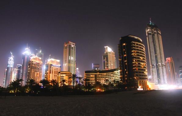 Картинка пляж, ночь, city, пальмы, дома, Дубай, Dubai, night, высотки, ОАЭ, песок.