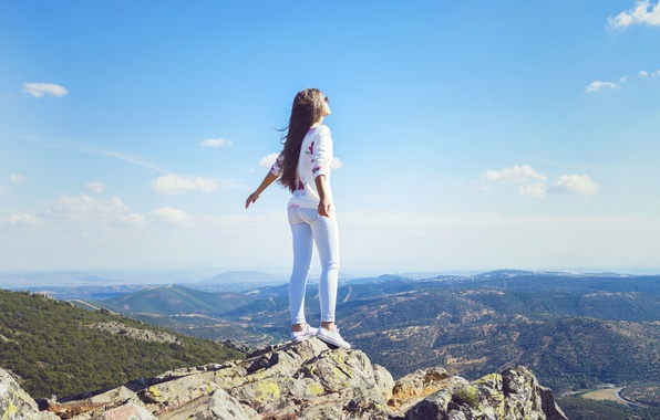 Картинка небо, девушка, облака, поза, ветер, волосы, гора, джинсы, горизонт, стоит