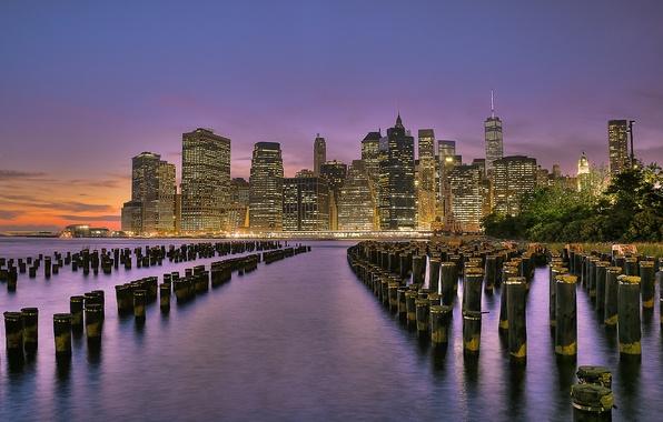 Картинка небо, закат, город, огни, река, берег, здания, Нью-Йорк, небоскребы, вечер, опоры, USA, США, оранжевое, New …