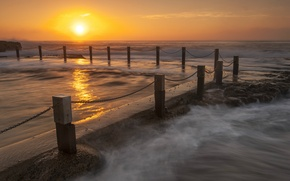 Картинка море, солнце, закат, оранжевый, океан, берег, побережье, Вечер, ограждение, прибой, цепи