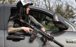 Обои девушка, лицо, волосы, рука, тату, кепка, автомобиль, штурмовая винтовка