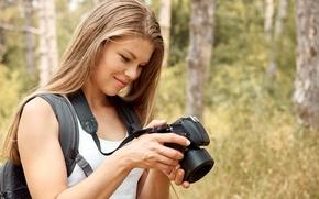 Картинка лес, девушка, деревья, майка, прическа, фотоаппарат, стоит, держит, на природе, боке, ранец, улыбается, русая