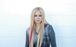 Картинка Девушка, Avril Lavigne, смотрит в камеру, известная рок певица, стоит над белой стеной, полоска в …