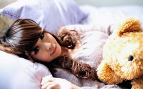 Обои девушка, улыбка, игрушка, подушки, медведь, постель, азиатка, солнечные лучи