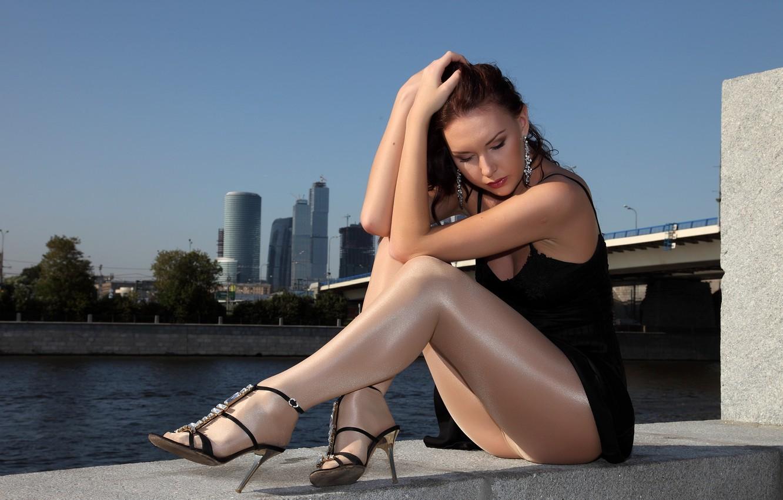 Фото обои небо, девушка, мост, город, река, небоскребы, серьги, платье, туфли, колготки, сидит