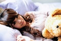 Картинка медведь, игрушка, постель, улыбка, солнечные лучи, подушки, девушка, азиатка